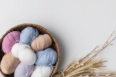Bolas coloreadas del hilado en cesta de mimbre y plantas secadas en el fondo blanco Imagen de archivo