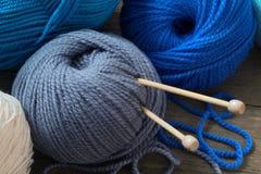 Bolas coloreadas del hilado y de las agujas que hacen punto en una tabla de madera Imagen de archivo libre de regalías