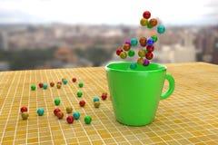 Bolas coloridas brillantes en la teja amarilla y en taza verde Foto de archivo libre de regalías