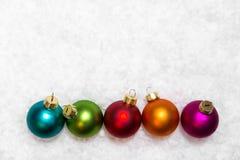 Bolas coloridas de la Navidad en fondo nevoso Fotos de archivo libres de regalías