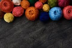 Bolas coloridas del hilado en fondo de madera imagen de archivo