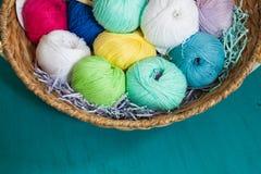 Bolas coloridas del hilado en la cesta en el fondo de madera Foto de archivo