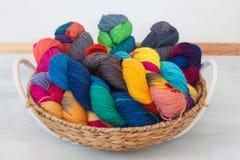 Bolas coloridas del hilado en la cesta en el fondo de madera Imagenes de archivo