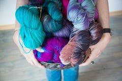 Bolas coloridas del hilado en la cesta en manos Fotos de archivo libres de regalías