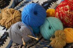 Bolas coloridas del hilado que mienten en un suéter hecho punto Imagen de archivo libre de regalías