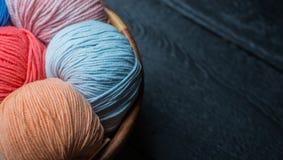 Bolas coloridas del hilo para obras de punto en cesta Fotografía de archivo
