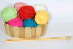 Bolas coloridas do fio de lãs em uma cesta decorativa e de agulhas de confecção de malhas de madeira na tabela foto de stock