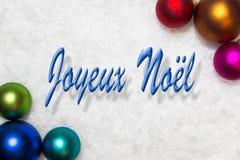 Bolas coloridas en la nieve, palabras francesas, feliz Cristo de la Navidad Foto de archivo libre de regalías