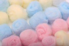 Bolas de algodón higiénicas azules, amarillas y rosadas en fila Imágenes de archivo libres de regalías