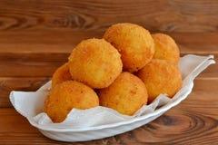 Bolas de Arancini en una placa Receta de las bolas de arroz frito Chuletas del arroz Fondo de madera de Brown Imagenes de archivo