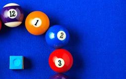 Bolas de bilhar em uma mesa de bilhar azul Fotos de Stock Royalty Free