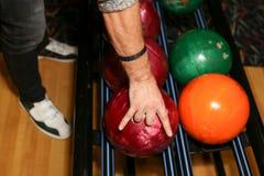 Bolas de boliches Pista de bowling O homem toma uma bola Cores vívidas Imagem de Stock Royalty Free