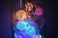 Bolas de brilho coloridas no fundo de vidro Imagens de Stock