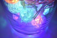 Bolas de brilho coloridas no fundo de vidro Fotografia de Stock Royalty Free