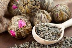 Bolas de chá verde com flores e a colher de madeira Foto de Stock Royalty Free
