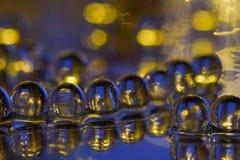 Bolas de cristal de azul y de amarillo en una superficie del espejo fotos de archivo libres de regalías
