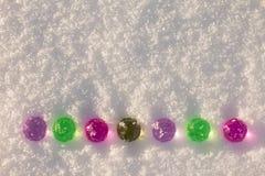 Bolas de cristal coloridas de la Navidad en el fondo brillante de la nieve fotos de archivo