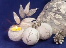 Bolas de cristal hermosas del ` s del Año Nuevo, malla brillante, la vela ardiente en un fondo azul - composición del ` s del Año Imagenes de archivo