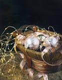 Bolas de cristal de la decoración del árbol de navidad en guirnalda de la cesta y de la luz en fondo de madera Foto de archivo libre de regalías