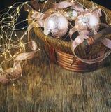 Bolas de cristal de la decoración del árbol de navidad en guirnalda de la cesta y de la luz en fondo de madera Imagen de archivo libre de regalías