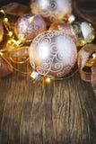 Bolas de cristal de la decoración del árbol de navidad y guirnalda ligera sobre fondo de madera Imagen de archivo