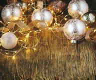 Bolas de cristal de la decoración del árbol de navidad y guirnalda ligera sobre fondo de madera rústico Imágenes de archivo libres de regalías