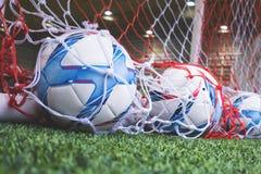 Bolas de futebol no objetivo do futebol no campo de treinamento do futebol Imagem de Stock