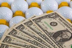 Bolas de golfe brancas na caixa amarela e no dinheiro dos E.U. Fotos de Stock