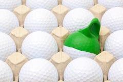 Bolas de golfe brancas na caixa para ovos Bola de golfe com tampão engraçado Fotografia de Stock Royalty Free
