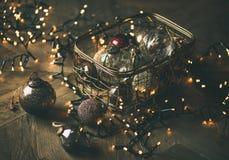 Bolas de la decoración del juguete del árbol de navidad en guirnalda de la caja y de la luz Fotografía de archivo libre de regalías