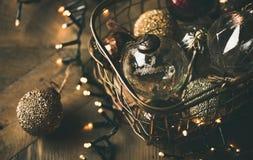 Bolas de la decoración del juguete del árbol de navidad en guirnalda de la caja y de la luz Imagen de archivo
