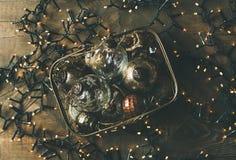 Bolas de la decoración de la Navidad en caja y guirnalda ligera del día de fiesta Fotografía de archivo libre de regalías