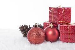 Bolas de la Navidad con la caja de regalo roja en blanco Imagenes de archivo