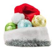 Bolas de la Navidad con el sombrero de Papá Noel aislado en la parte posterior del blanco Foto de archivo libre de regalías