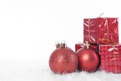 Bolas de la Navidad con la caja de regalo en la tabla blanca Imagen de archivo