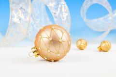 Bolas de la Navidad con la cinta en nieve Imágenes de archivo libres de regalías