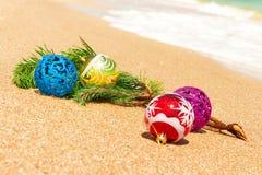 Bolas de la Navidad con la ramita del abeto en la arena Foto de archivo