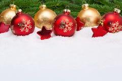 Bolas de la Navidad con las estrellas en fondo de la nieve Fotografía de archivo