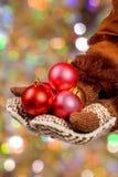 Bolas de la Navidad del asimiento de las manos Foto de archivo libre de regalías