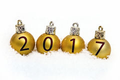 Bolas de la Navidad del oro con las inscripciones de la nieve Imagen de archivo libre de regalías