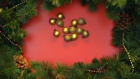 Bolas de la Navidad del oro que forman el círculo en adornado con el fondo de las ramas de la picea almacen de video