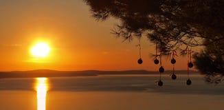 Bolas de la Navidad en la puesta del sol en el mar adriático Imagen de archivo libre de regalías