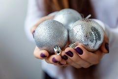 Bolas de la Navidad en las manos Fotos de archivo
