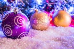 Bolas de la Navidad en nieve fondo de ramas borrosas Foto de archivo libre de regalías