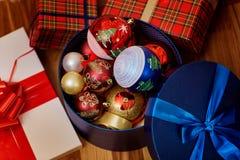 Bolas de la Navidad en una caja con un regalo con las cintas en un nuevo feliz Fotos de archivo libres de regalías