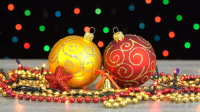 Bolas de la Navidad hermosa y decoraciones rojas y de oro en un piso de madera contra la guirnalda que destella colorida en un ne metrajes