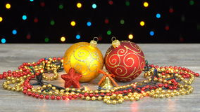 Bolas de la Navidad hermosa y decoraciones rojas y de oro en un piso de madera contra la guirnalda que destella colorida en un ne almacen de video