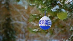 Bolas de la Navidad que cuelgan en las ramas del pino cubiertas con nieve almacen de video
