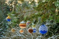 Bolas de la Navidad que cuelgan en las ramas del pino cubiertas con nieve Fotos de archivo libres de regalías