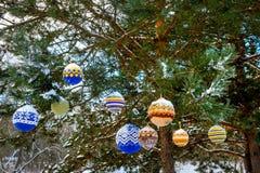 Bolas de la Navidad que cuelgan en las ramas del pino cubiertas con nieve Fotografía de archivo libre de regalías